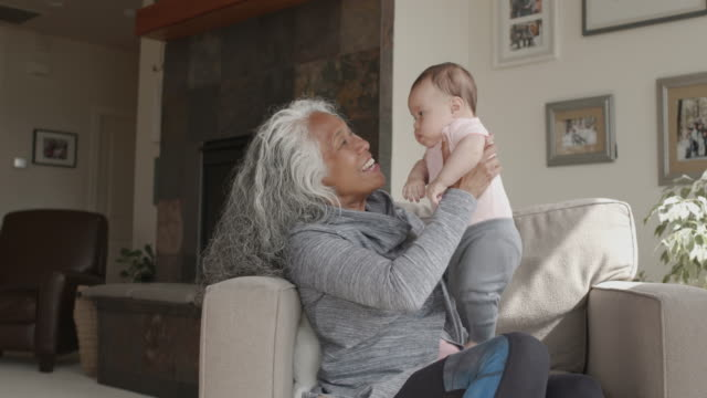 beautiful retired senior woman playing affectionately with cute baby granddaughter - nonna video stock e b–roll