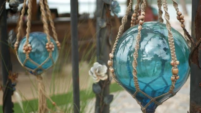 vídeos de stock, filmes e b-roll de linda decoração retrô e plantas para o jardim. conjunto de boias azuis do mar de vidro e macrame em estilo vintage para decoração de quintal. fundo moderno e elegante. - rústico