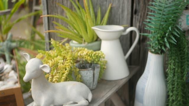 vídeos de stock, filmes e b-roll de linda decoração retrô e plantas para o jardim. conjunto de vasos e figuras cerâmicas em estilo vintage para decoração de quintal. fundo moderno e elegante. - rústico