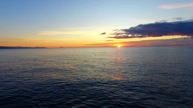 aerial: beautiful ripples on sea water surface at sunrise - krajobraz morski filmów i materiałów b-roll