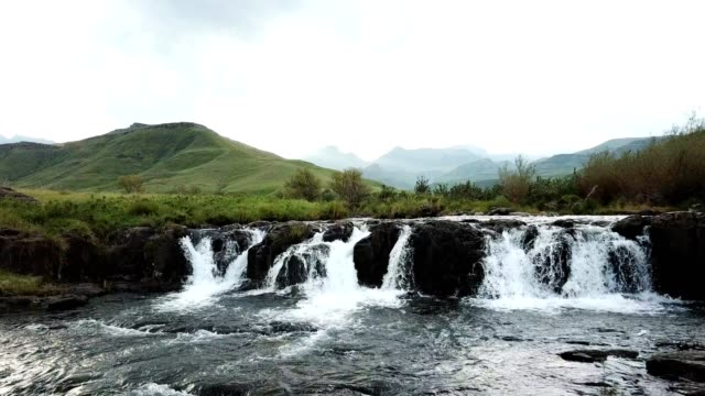 Beautiful river flowing over a small waterfall A beautiful river flows through the foothills of the mountains, the river falls over a small waterfall into a rockpool natal stock videos & royalty-free footage