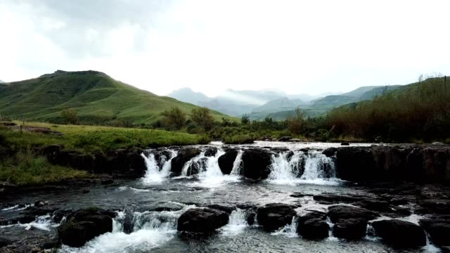 Beautiful river flowing through the foothills of the large mountains A beautiful river flows through the foothills of the mountains, the river falls over a small waterfall into a rockpool natal stock videos & royalty-free footage