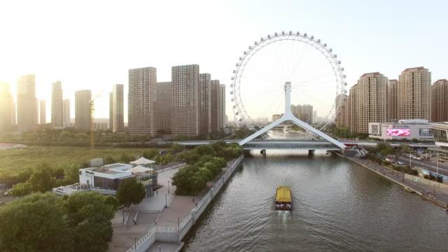 beautiful river through modern buildings and ferris wheel video