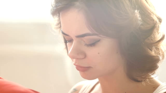 Beautiful romantic and slightly sad girl holding a red pillow and thinking about something. video