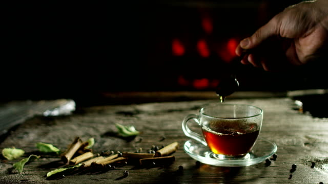 beautiful romantic composition of herbal teas and tea while it is being poured on an old wooden cutting board with spice in the background and a fireplace - tea cup stock videos & royalty-free footage