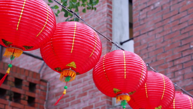 beautiful round red lantern hanging on old traditional street, concept of chinese lunar new year festival, close up. - китайский фонарь стоковые видео и кадры b-roll