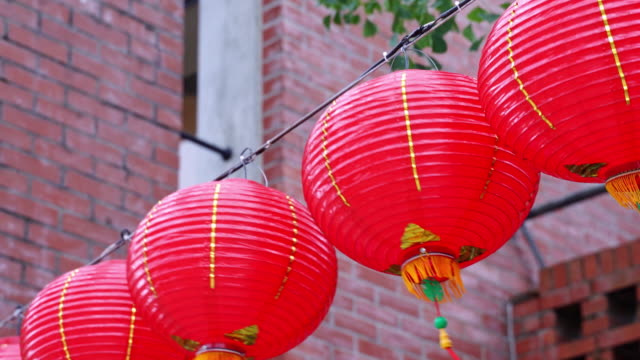 beautiful round red lantern hanging on old traditional street, concept of chinese lunar new year festival. - китайский фонарь стоковые видео и кадры b-roll