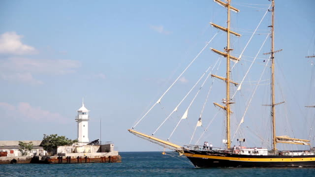 beautiful sailing ship on the background of the Yalta lighthouse video