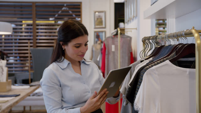 Beautiful sales woman at a clothing store checking inventory holding a tablet Beautiful sales woman at a clothing store checking inventory holding a tablet - Retail concepts department store stock videos & royalty-free footage