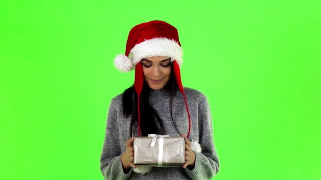 カメラへのクリスマス プレゼントを持って笑みを浮かべて美しいサンタガール - サンタの帽子点の映像素材/bロール