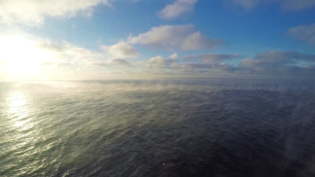 Beautiful scene: blue sunny sky with сumulus clouds, steam over the sea, the view from the boat video