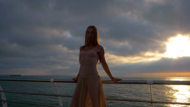 Beautiful scene of a dancing ballerina in beige silk dress and pointe on embankment above ocean or sea beach at sunrise or sunset. Young beautiful blonde sensual woman with long hair practicing stretching and classic exercises. SLOW MOTION - video