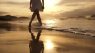 istock Beautiful scene of a low section of woman walking on ocean beach at sunset 1216160027