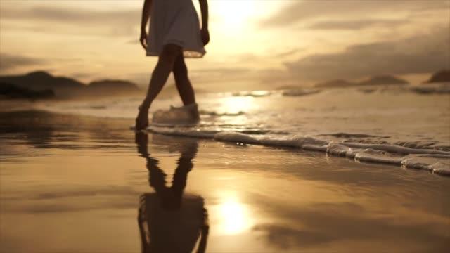 красивая сцена низкой части женщины, идущей по океану пляж на закате - элемент здания стоковые видео и кадры b-roll
