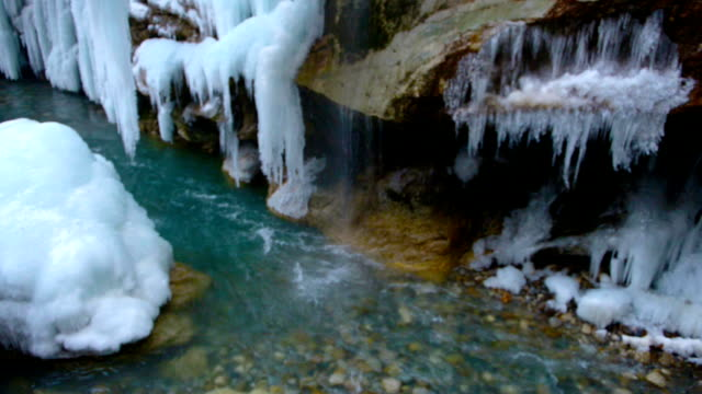 beautiful scene of frozen waterfall with blue icicles and turquoise river, spring concept video