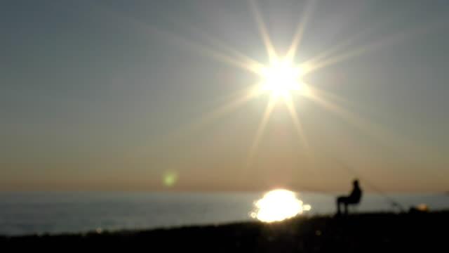 beautiful scene with fisherman silhouette with rod sitting on sea beach - żabnicokształtne filmów i materiałów b-roll
