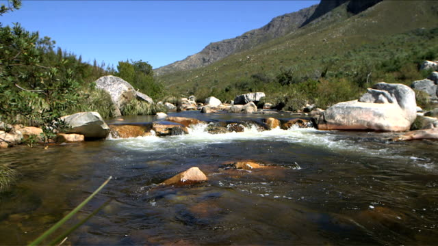 Beautiful, scenic mountain side river flowing over rocks, before camera moves up to focus on the mountain alongside video