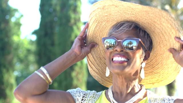 vidéos et rushes de belle femme africaine-américaine âgée avec des lunettes de soleil - chapeau