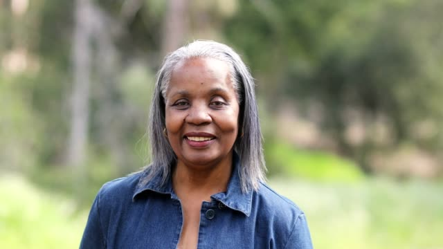 beautiful senior black woman smiling outdoors - woman portrait forest video stock e b–roll