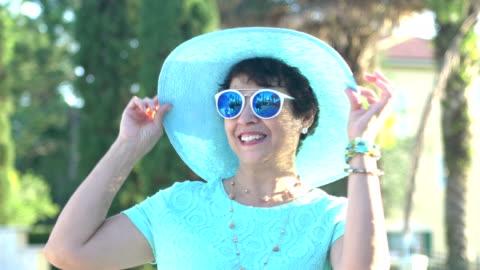 vidéos et rushes de belle femme hispanique âgée avec des lunettes de soleil, chapeau - chapeau