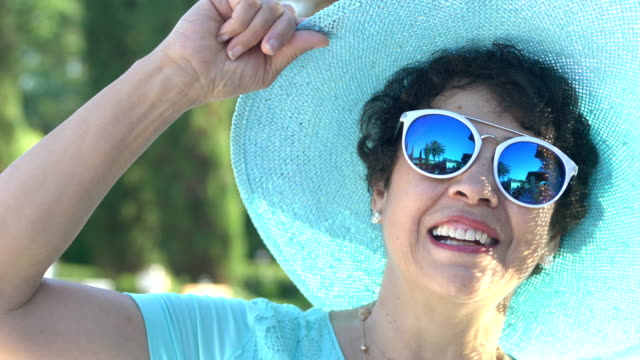 Beautiful senior Hispanic woman with sunglasses, hat