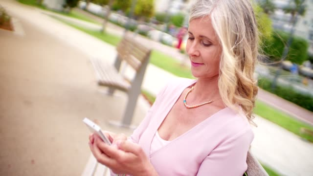 vídeos de stock e filmes b-roll de beautiful senior woman in park texting on her smartphone - mulheres maduras