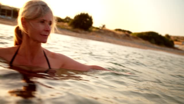 Beautiful senior woman swimming in the sea at sunset video