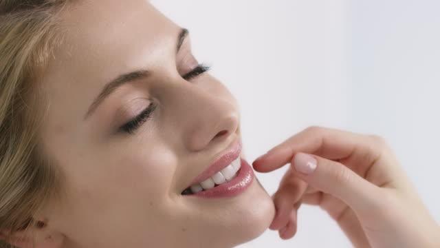 vídeos y material grabado en eventos de stock de hermosa mujer sensual apoyado en pared - sonrisa con dientes