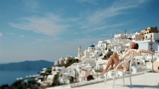 Beautiful sexy brunette bride in robe sitting on the white chair and stretches enjoying the sea and mountains in background video