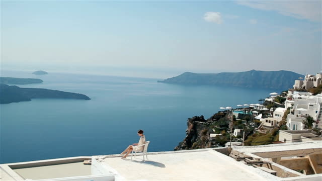 Beautiful sexy brunette bride in robe sitting with her legs crossed  at the roof with sea and mountains in background video