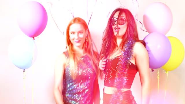 Chicas lindas sexy bailando con apoyos en la cabina de la foto - vídeo