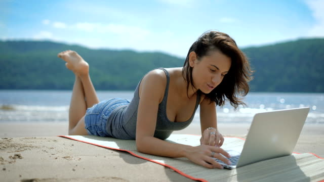 A beautiful sexy joyful smiling lady is laying on her tommy at a beach using laptop video