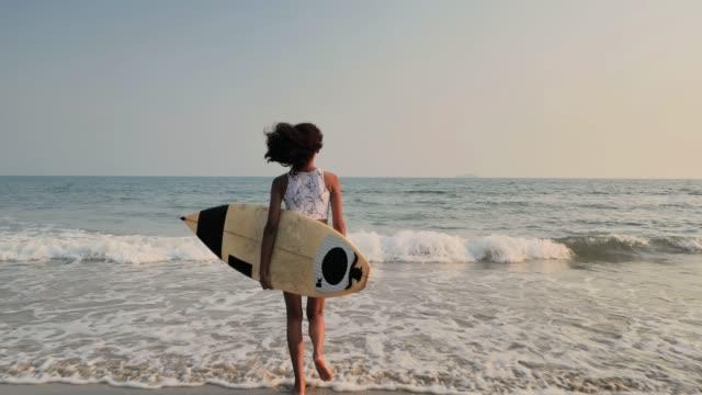 gün batımında sahilde güzel seksi sörfçü kız. spor cinemagraphs - kızlar stok videoları ve detay görüntü çekimi