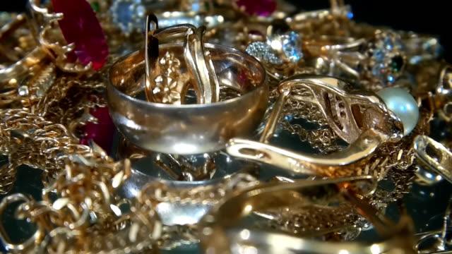 vidéos et rushes de beaux bijoux brillants et étincelants d'or sur une surface de verre avec l'éblouissement dans des gemmes - joaillerie