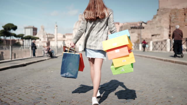 vídeos de stock e filmes b-roll de beautiful shopaholic girl walking in milan center with shopping bags full of purchases. big sales in shopping mall, happiness and joy. pretty woman dancing in milan center with colorful shopping bags - tote bag
