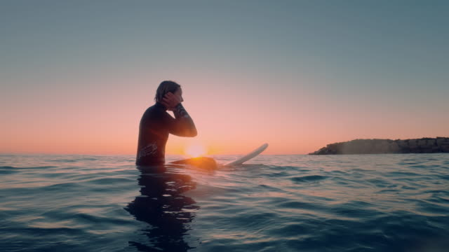 青い海のサーフボードに座っている女性サーファーの水からの美しいショットは、日没/日の出で次の大きな波を待っています。 - サーフィン点の映像素材/bロール