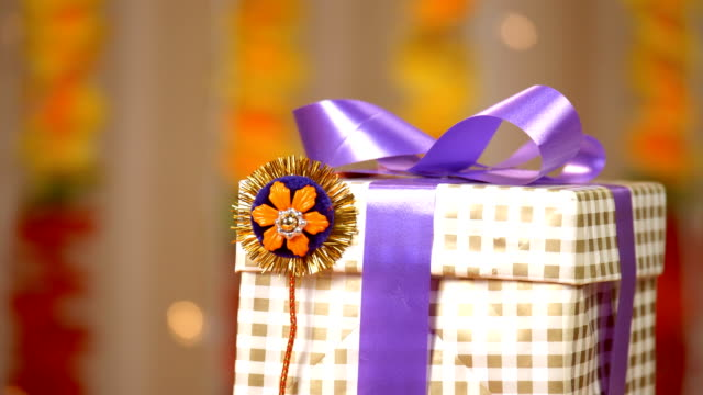 A beautiful shot of a handmade rakhi and a wrapped gift for Raksha Bandhan
