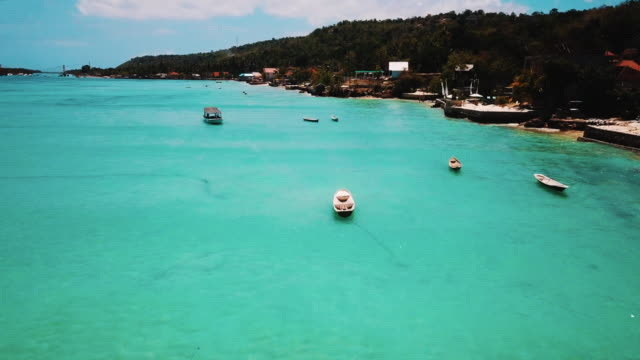 Beautiful Shot Of Above Crystal Clear Water To Reveal Boats And Tropical Island Of Nusa Ceningan video