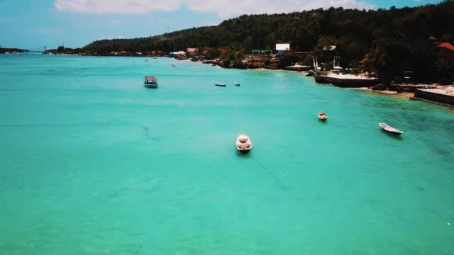 Schöne Aufnahme von oben Kristall klares Wasser, Boote und tropische Insel Nusa Ceningan offenbaren – Video