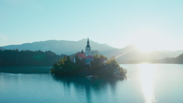 a beautiful shot of an island with a church in the middle of the lake bled with sun flare shinning into the camera. - словения стоковые видео и кадры b-roll