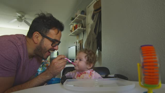 Beautiful shot of father playing with baby daughter as he feeds her with spoon video