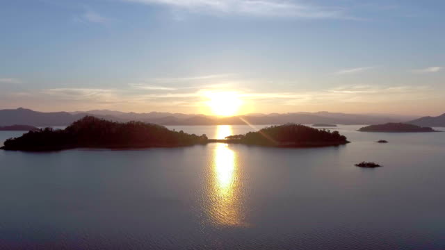 Beautiful shot of sunset on lake with small island at dusk, Aerial dolly shot video