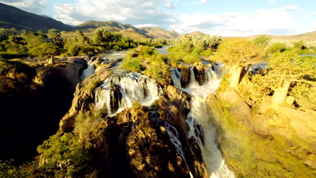 HELI Beautiful Shot Of The Epupa Falls HD1080p: AERIAL HELI shot of the Epupa falls with surrounding landscape. Time Warp effect of moving up with the multicopter. Namibia. Africa. namibia stock videos & royalty-free footage