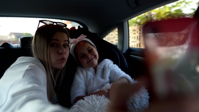 vidéos et rushes de beaux frères et soeurs prenant un selfie dans une voiture - voiture blanche