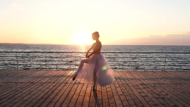 vacker siluett av ballerina i lång balett tutu och pointe på vallen ovanför havet eller havet vid soluppgången. dans, öva med solen stiger på bakgrunden - på tå bildbanksvideor och videomaterial från bakom kulisserna
