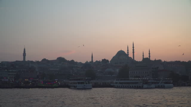 Beautiful silhouette View of touristic landmarks at at Eminönü (Turyol)  harbour at sunset among air pollution