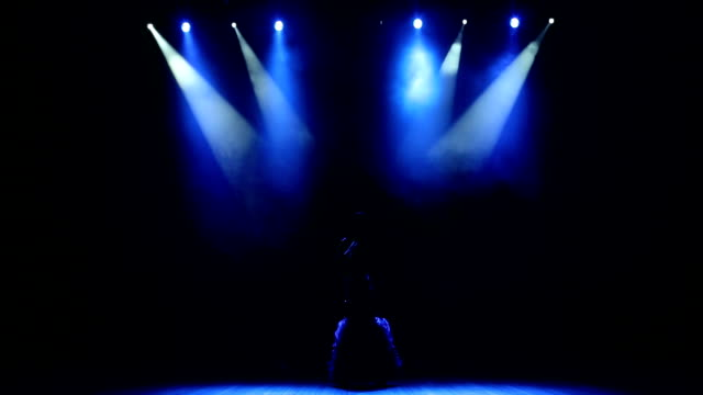 Beautiful singer on stage with blue light. A beautiful singer on stage in the dark under the light of a blue spotlight. low lighting stock videos & royalty-free footage