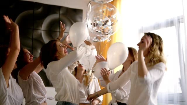 beautiful six women on a hen party are hanging out together. dancing and having fun with baloons. all in identical clothes,jeans and white blouses. indoors. happy, carefree - bachelorette party stock videos & royalty-free footage