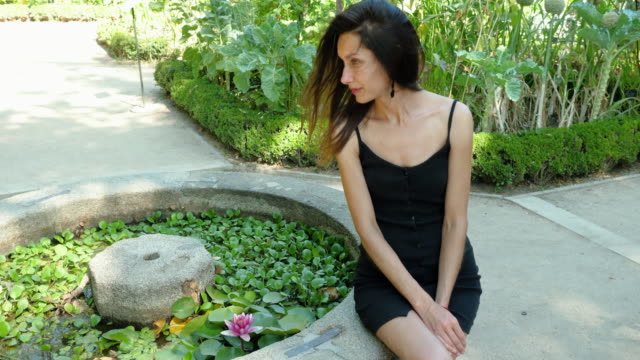 A beautiful slender girl is sitting by a pond with water lilies. Madrid. Spain. 4K