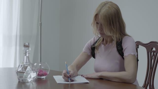vacker smal blond kvinna i en ortopedisk korset för ryggen sitta på bordet och skriva ett brev - brev dokument bildbanksvideor och videomaterial från bakom kulisserna